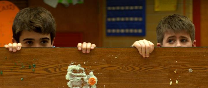 still from Incident at Public School 173 - 2 boys peering over food-stained table